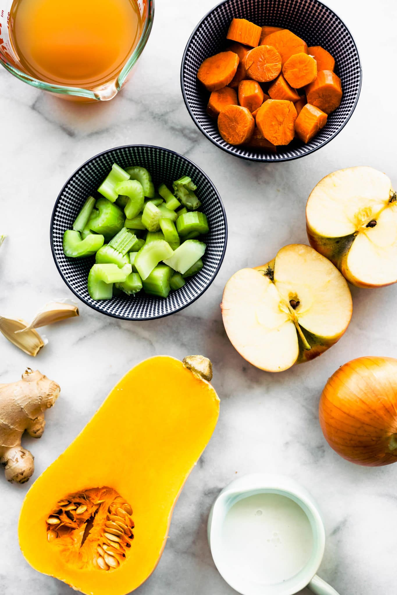 overhead photo of diced celery and carrot in bowls, sliced apple, yellow onion, sliced butternut squash, broth, and cream in jar on marble backdrop