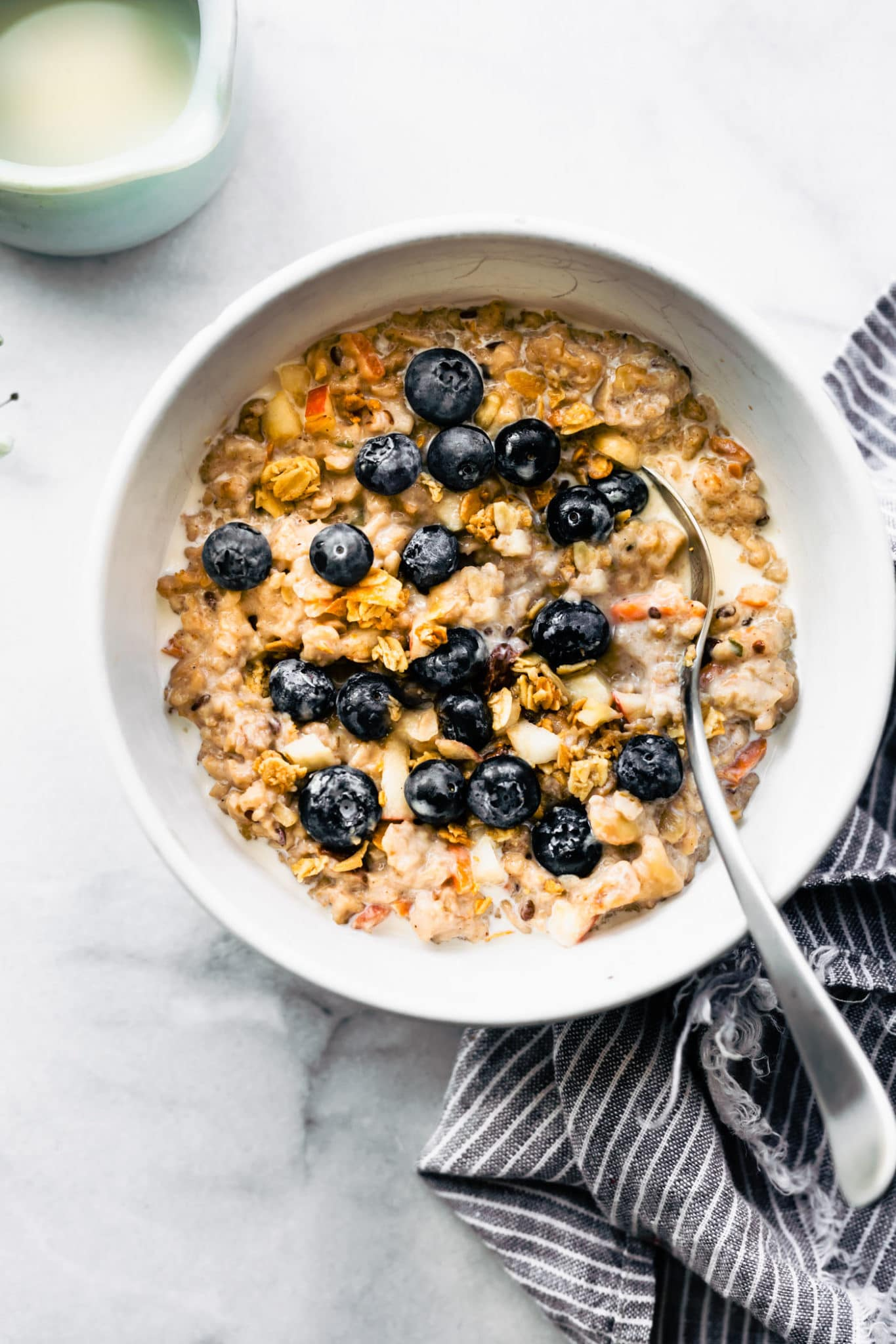 superfood instant pot oatmeal served in a white bowl topped with fresh blueberries and served with a spoon