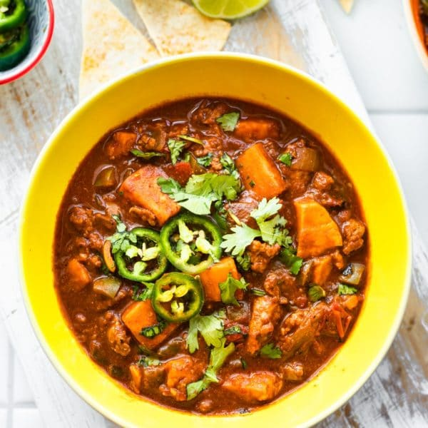 sweet potato turkey chili in a bowl topped with cilantro and jalapeno