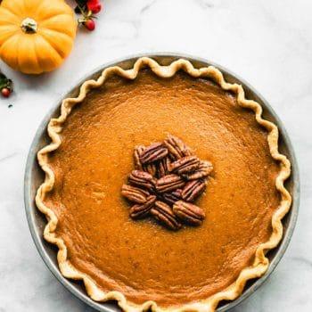 Whole gluten-free pumpkin pie with pecans on top